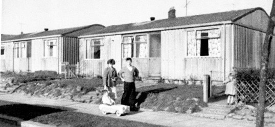 A family outside one of the prefabs